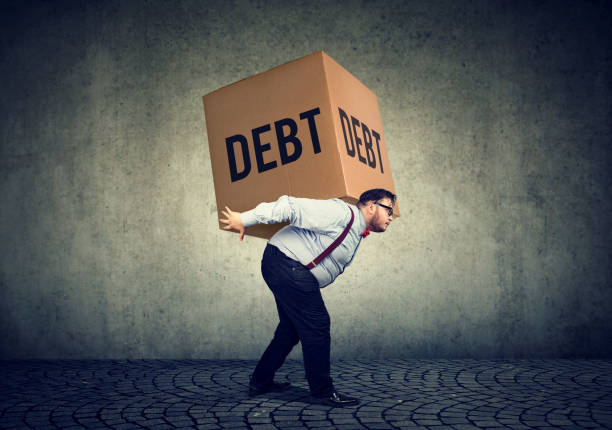Business man carrying heavy box of debt stock photo