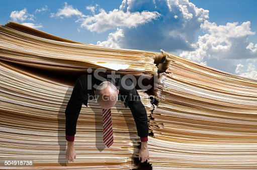 481644192 istock photo Business man caught under pile of files 504918738