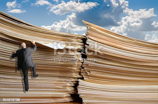 481644192 istock photo Business man climbing up a pile of files 504918796