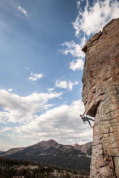 Business man climbs rock face stock photo