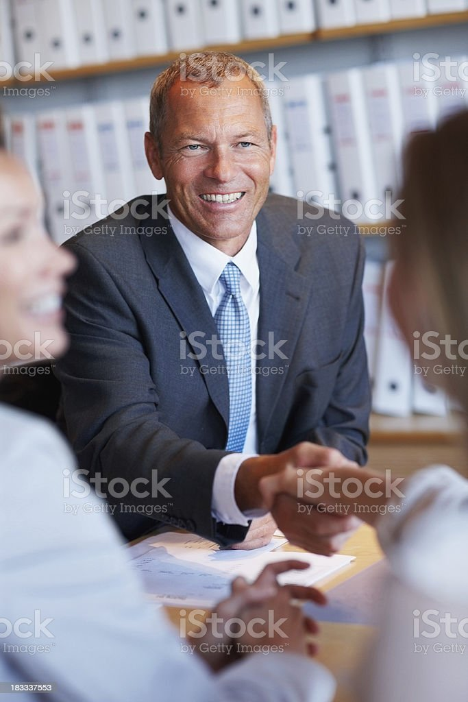 Business man congratulating a co worker during meeting royalty-free stock photo