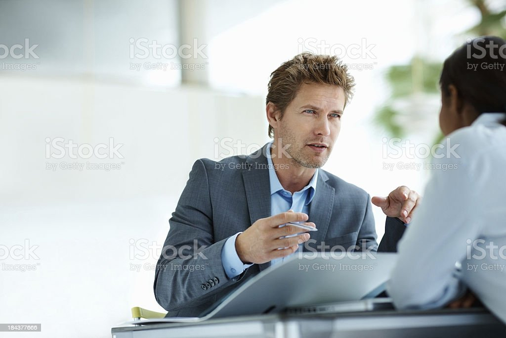 Business man conversing with female associate royalty-free stock photo