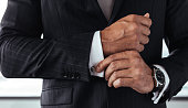 Closeup of businessman in formal suit correcting a sleeve. Male hands fixing white shirt cuffs sleeves.