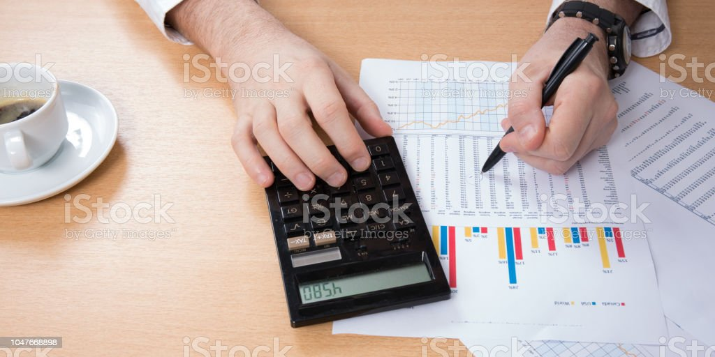 business man counts on a close-up calculator, cafe, laptop, business, finance, banking at home stock photo