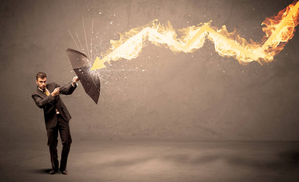 Business man defending himself from a fire arrow with an umbrella stock photo