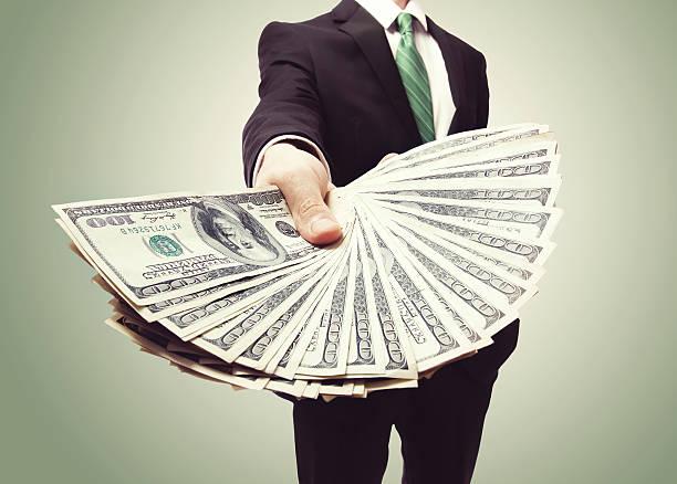 деловой человек отображение распространения наличных в - dollar bill стоковые фото и изображения