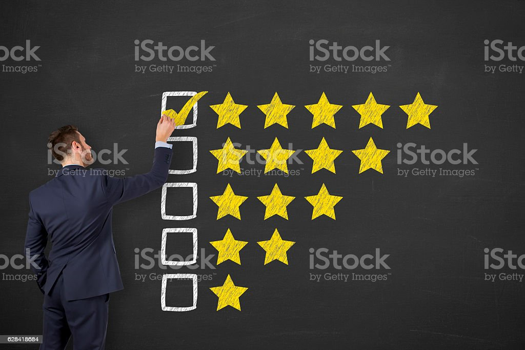 Business Man Drawing Customer Satisfaction on Blackboard Background stock photo