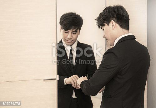 istock Business man dressing up for work in front of the mirror 817274278