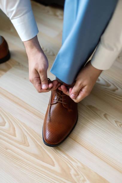 geschäftsmann verkleidet sich mit klassischen, eleganten schuhen. bräutigam tragen am hochzeitstag, die schnürsenkel binden und vorbereiten - knotenkleid stock-fotos und bilder