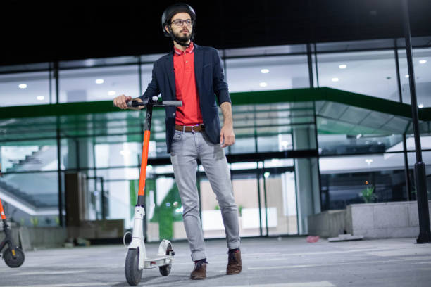 Business man driving his electric push scooter
