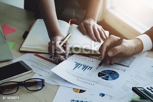 925942192istockphoto business man Explain analyze the company's sales plan and business woman by use pen, computer laptop, calculator, stock market chart on wood desk in conferance. 911626374