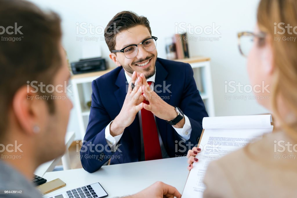 Business man explaining terms of contract to his clients in the office. - Royalty-free Adult Stock Photo