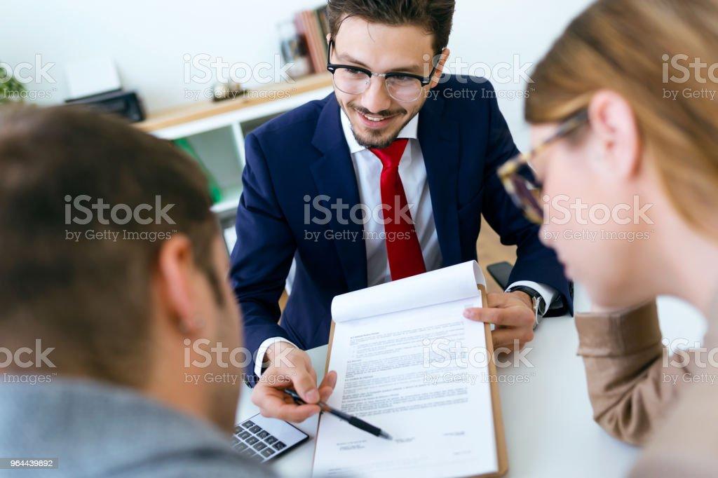 Homem de negócios, explicando os termos do contrato para seus clientes no escritório. - Foto de stock de Adulto royalty-free