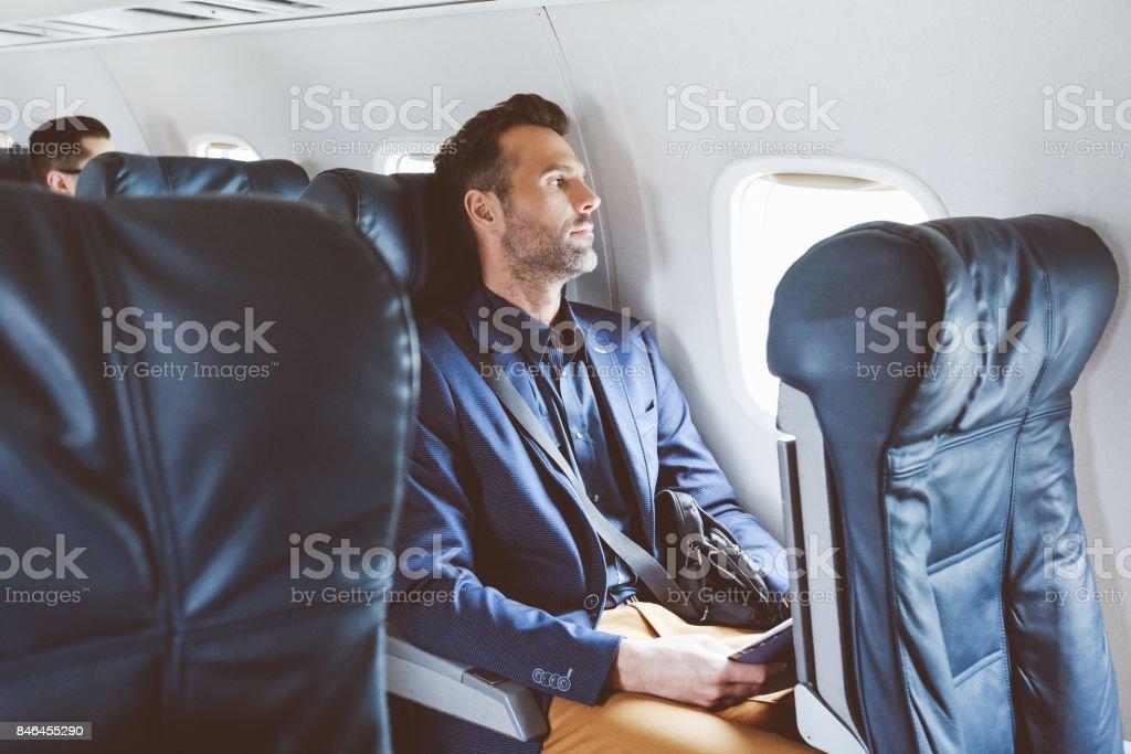 Hombre de negocios volando en avión - foto de stock