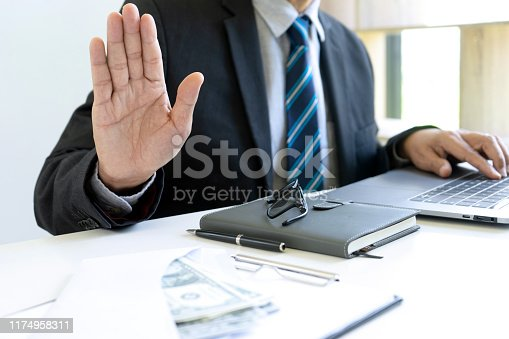 848170878istockphoto Business man give bribe to the officer 1174958311