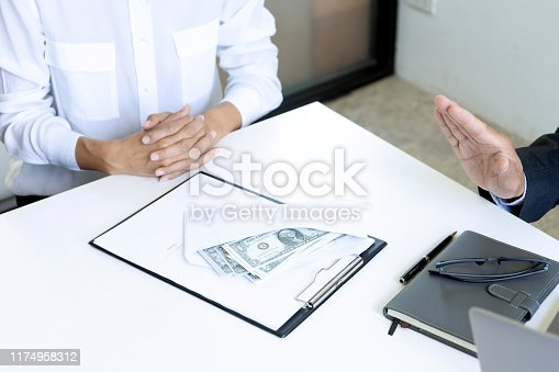 848170878istockphoto Business man give bribe to the officer 1174958312