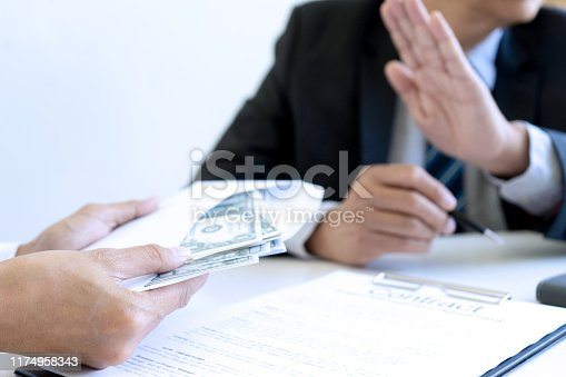 848170878istockphoto Business man give bribe to the officer 1174958343