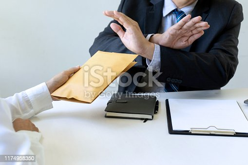 848170878istockphoto Business man give bribe to the officer 1174958350