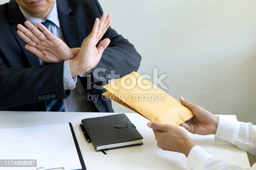 848170878istockphoto Business man give bribe to the officer 1174958387