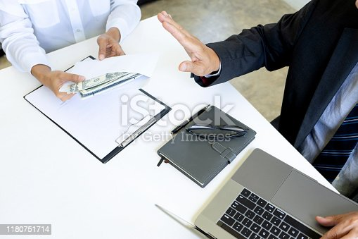 848170878istockphoto Business man give bribe to the officer 1180751714