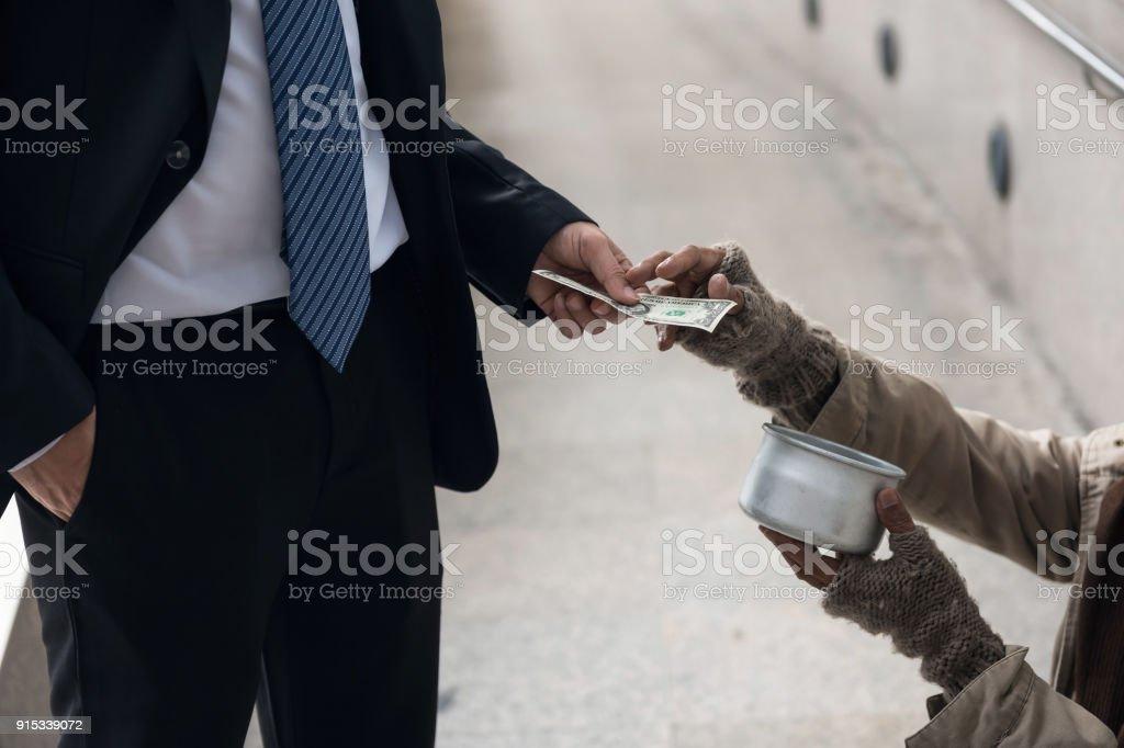 Business-Mann geben Geld an Bettler – Foto