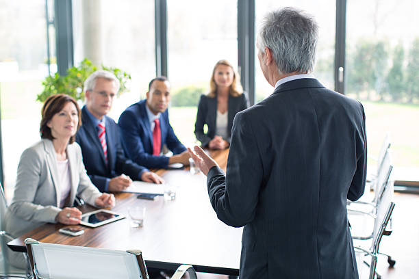 Business man giving a presentation Business man giving a presentationhttp://bit.ly/1baBzlj governing board stock pictures, royalty-free photos & images