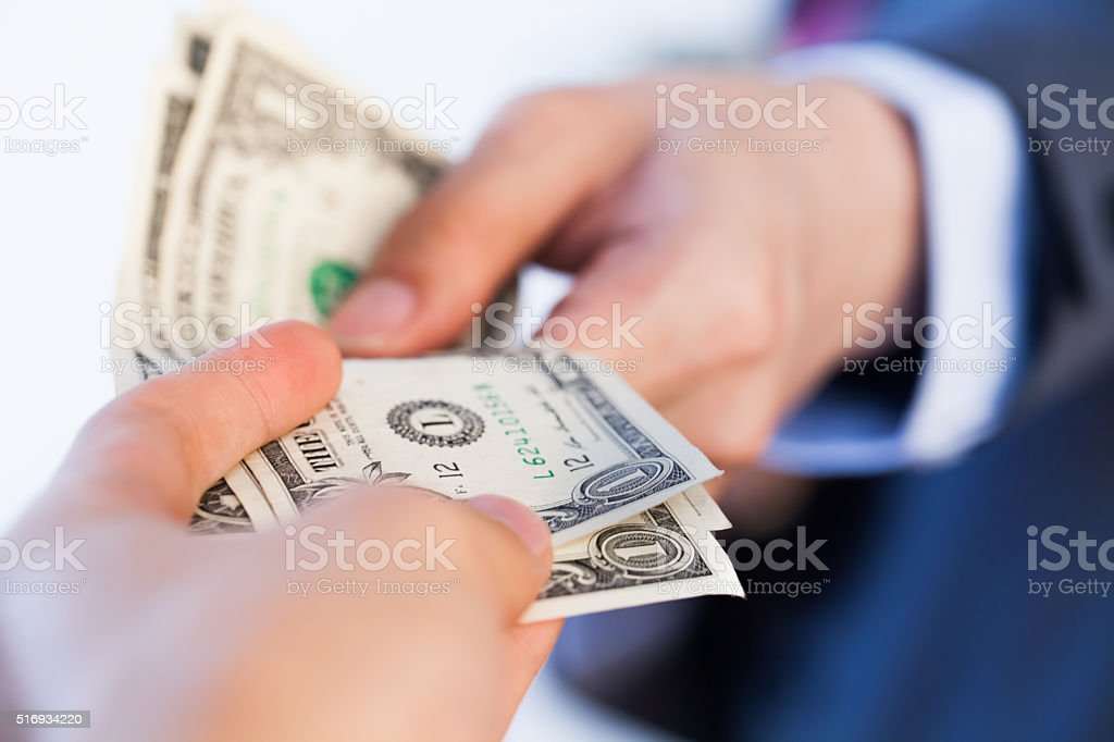 Business man giving bank notes to another person stock photo