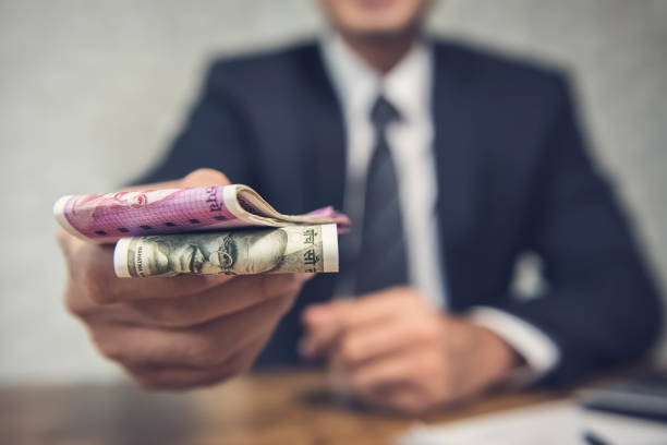 A business man giving money in the form of Idian Rupees A businessman giving money in the form of Indian Rupees for services rendered as per a signed contract. borrowing stock pictures, royalty-free photos & images