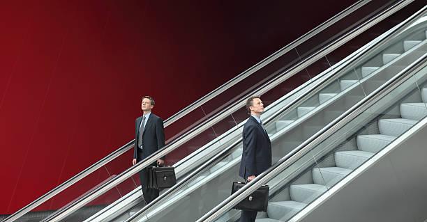 uomo d'affari andando su e giù per le scale mobili, il concetto di scelta - escalator foto e immagini stock