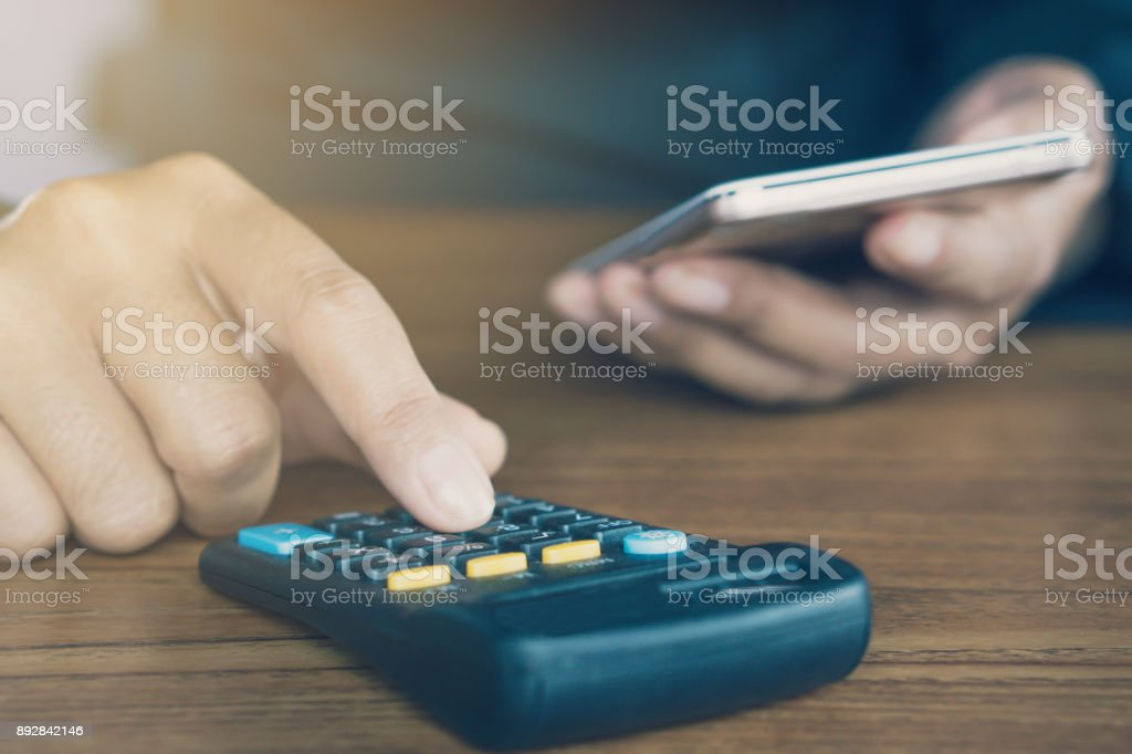 business man hand calculating his monthly expenses during tax season with calculator and smart phone stock photo