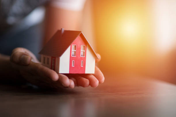 Business man hand hold the house model saving small house stock photo
