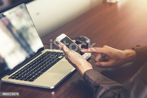 1016971522istockphoto business man hand holding and using smartphone in the office. 680023976