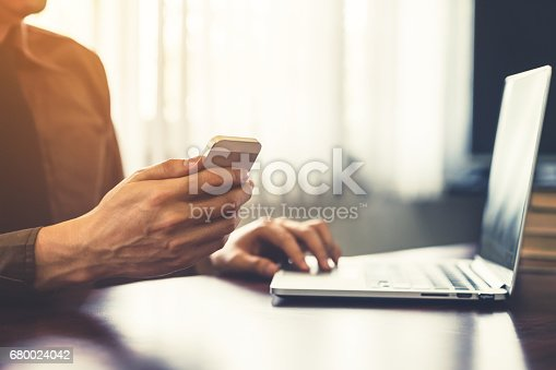 1016971522istockphoto business man hand holding and using smartphone in the office. 680024042