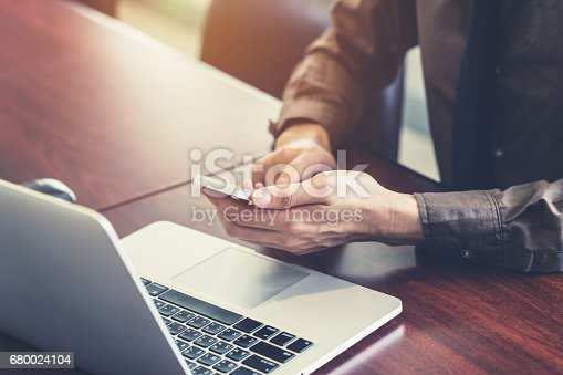 1016971522istockphoto business man hand holding and using smartphone in the office. 680024104
