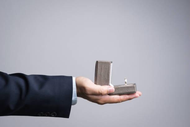 business mann hand hält box mit ring - hochzeitsbox stock-fotos und bilder