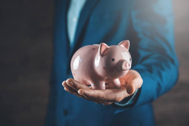 Geschäftsmann Hand hält Sparschwein – Foto