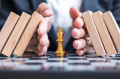 istock Business man hand protect Chess King figure and Stopping Falling wooden Blocks or Dominoes. Business, Risk Management, Solution, economic regression, Insurance, strategy and Interruption Concepts 1297953298