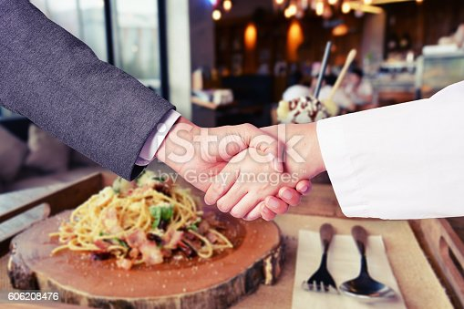 istock business man hand shake with chef 606208476