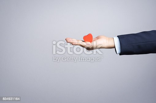 istock Business man hand with wooden red heart object 834931164
