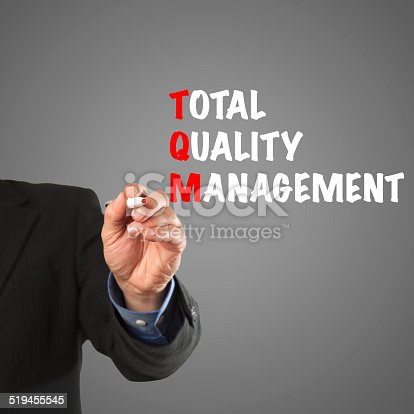Male hand in business wear holding a thick pen, writing the terms Total Quality Management