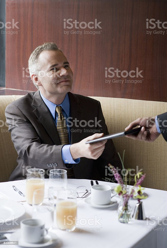 Business man handing check to waiter. royalty-free stock photo