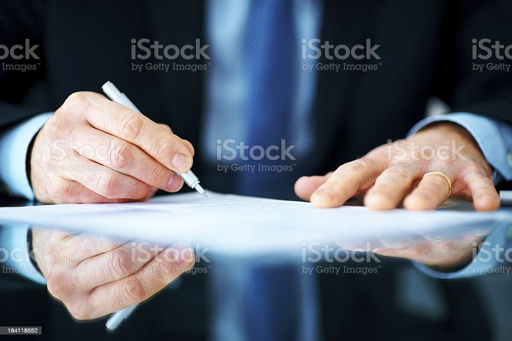 Business man hands signing on document at his desk stock photo