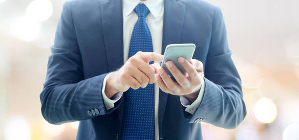 Business man hands using smart phone over blur office with copy space background, businessman on phone stock photo
