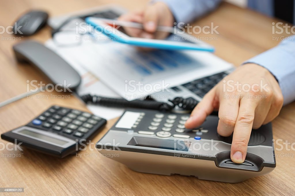 business man hanging up the phone while working on tablet stock photo