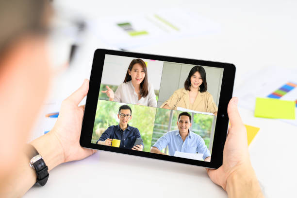business man have a meeting with Asain colleagues about plan in video conference via tablet stock photo