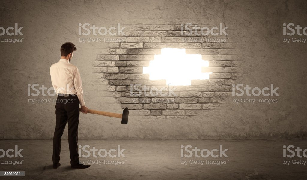 Business man hitting brick wall with hammer and opening a hole stock photo