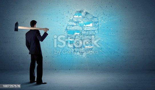 istock Business man hitting brick wall with huge hammer 1007257576