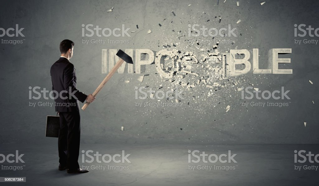 Business man hitting impossible sign with hammer stock photo