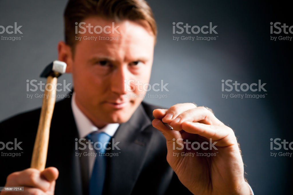 business man 'hitting nail on the head' stock photo
