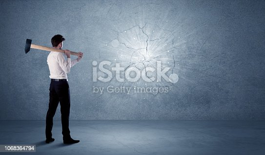 istock Business man hitting wall with a hammer 1068364794